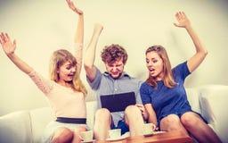 Amis heureux réussis avec le comprimé à la maison Image libre de droits