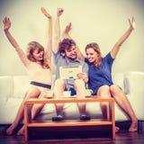 Amis heureux réussis avec le comprimé à la maison Photo stock