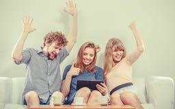 Amis heureux réussis avec le comprimé à la maison Photographie stock libre de droits