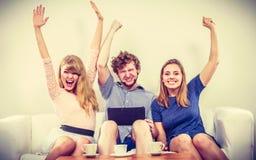 Amis heureux réussis avec le comprimé à la maison Photographie stock