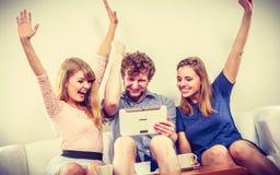Amis heureux réussis avec le comprimé à la maison Photos libres de droits