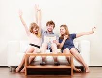 Amis heureux réussis avec le comprimé à la maison Photo libre de droits
