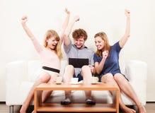 Amis heureux réussis avec le comprimé à la maison Photos stock