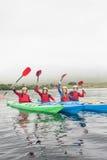 Amis heureux ramant sur un lac Images stock