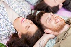 Amis heureux refroidissant sur la couverture de pique-nique à l'été Image libre de droits
