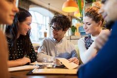 Amis heureux regardant au menu le restaurant Image libre de droits