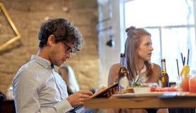Amis heureux regardant au menu le restaurant Image stock