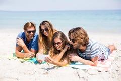 Amis heureux regardant dans le téléphone portable tout en se trouvant la plage Photographie stock