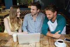 Amis heureux regardant l'ordinateur portable numérique tout en se reposant par la table Photos stock
