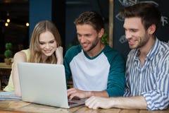 Amis heureux regardant l'ordinateur portable numérique tout en se reposant sur la chaise Images stock