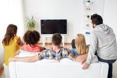 Amis heureux regardant la TV à la maison Images libres de droits