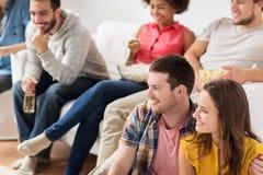 Amis heureux regardant la TV à la maison Image libre de droits