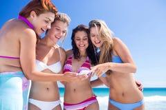 Amis heureux regardant le smartphone Photographie stock libre de droits