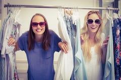 Amis heureux regardant par le support de vêtements Photos stock
