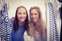 Amis heureux regardant par le support de vêtements Photo stock