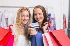 Amis heureux remettant une carte de crédit Photographie stock