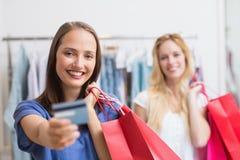Amis heureux remettant une carte de crédit Photographie stock libre de droits