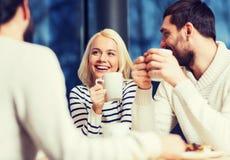 Amis heureux rencontrant et buvant du thé ou du café Photo libre de droits