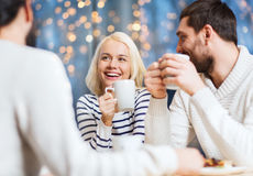 Amis heureux rencontrant et buvant du thé ou du café Photo stock