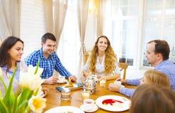 Amis heureux rencontrant et parlant et mangeant des desserts sur une table Images stock