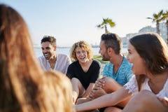 Amis heureux reposant l'extérieur riant ensemble Images stock