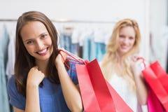 Amis heureux retenant des sacs à provisions Image stock