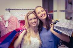 Amis heureux retenant des sacs à provisions Images stock