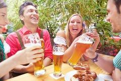 Amis heureux riant en bière Images libres de droits