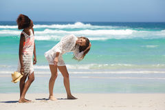 Amis heureux riant la marche sur la plage Photos stock