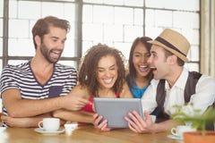 Amis heureux riant tout en regardant le comprimé Image stock