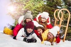 Amis heureux s'étendant à la neige dans la forêt d'hiver Image libre de droits