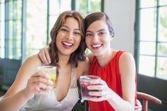 Amis heureux s'étreignant tout en tenant des verres de cocktail Image stock