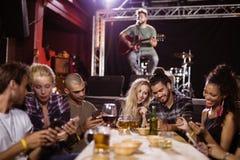 Amis heureux s'asseyant à la table avec le musicien à l'arrière-plan Images libres de droits