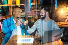 Amis heureux s'asseyant à la table et souriant tout en buvant de la bière Photos stock