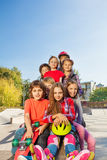 Amis heureux s'asseyant avec des planches à roulettes et des casques Photographie stock libre de droits