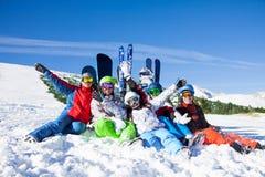 Amis heureux s'asseyant avec des surfs des neiges et des skis Images stock