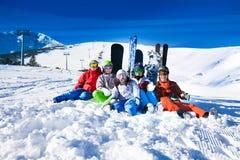 Amis heureux s'asseyant avec des surfs des neiges et des skis Photo stock
