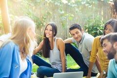 Amis heureux s'asseyant avec l'ordinateur portable dehors Image libre de droits