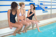 Amis heureux s'asseyant côte à côte à la piscine Photographie stock