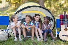 Amis heureux s'asseyant dans la tente Images stock