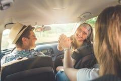 Amis heureux s'asseyant dans la voiture et voyageant ensemble Images stock
