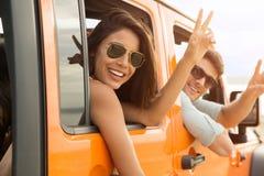 Amis heureux s'asseyant dans une voiture et montrant le geste de paix Photos libres de droits