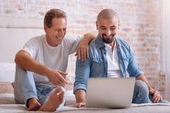 Amis heureux s'asseyant devant l'ordinateur portable Images libres de droits