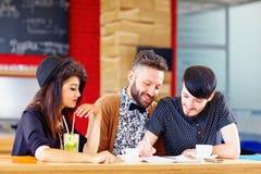 Amis heureux s'asseyant en café, étudiant Photographie stock libre de droits