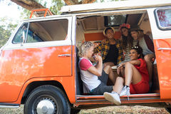 Amis heureux s'asseyant ensemble dans le camping-car Image libre de droits