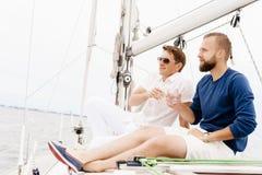 Amis heureux s'asseyant ensemble sur une plate-forme d'un yacht Photo stock
