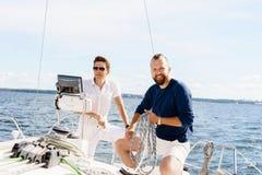 Amis heureux s'asseyant ensemble sur une plate-forme d'un yacht Images stock
