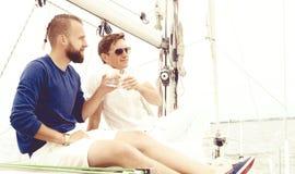 Amis heureux s'asseyant ensemble sur une plate-forme d'un yacht et ayant a Photographie stock libre de droits
