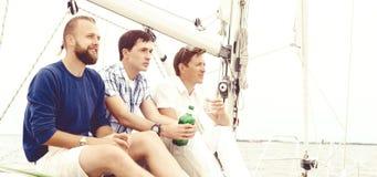 Amis heureux s'asseyant ensemble sur une plate-forme d'un yacht et d'un boire Photographie stock