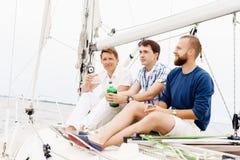 Amis heureux s'asseyant ensemble sur une plate-forme d'un yacht et buvant une boisson alcoolisée Photographie stock
